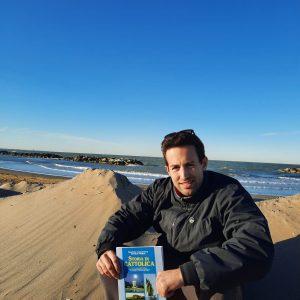 Marco seduto su una duna di sabbia, che in inverno protegge la costa dalle mareggiate